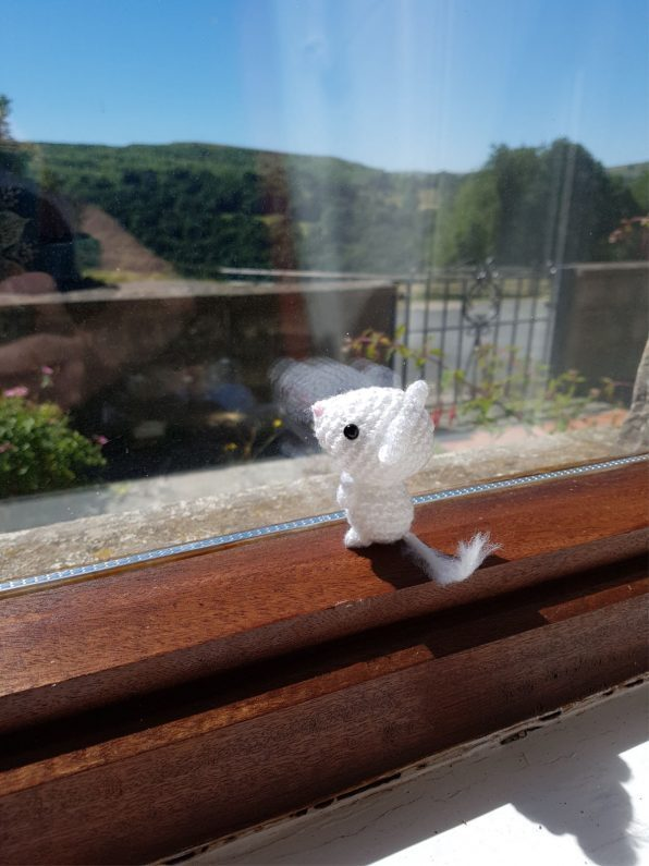 amigurumi mouse looking out of the window
